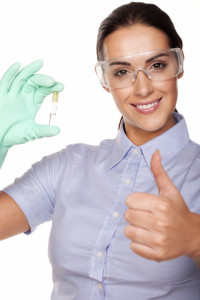 Beautiful smiling young female lab technician giving a thumbs up of success while holding up a test tube in her gloved hand isolated on white