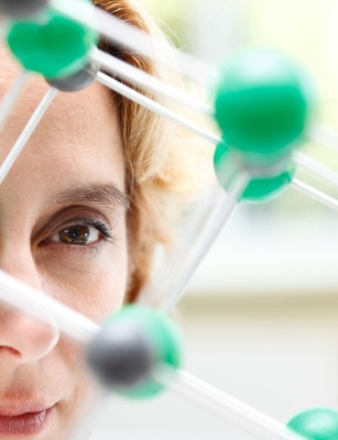 Researcher looking at a green molecule on a white background